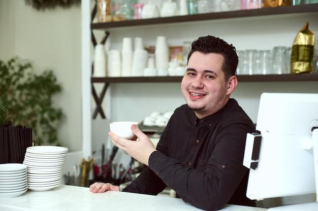 Der junge hübsche barista lächelt und hält eine tasse kaffee