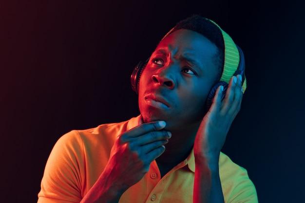 Der junge hübsche ernsthafte traurige hipster-mann, der musik hört