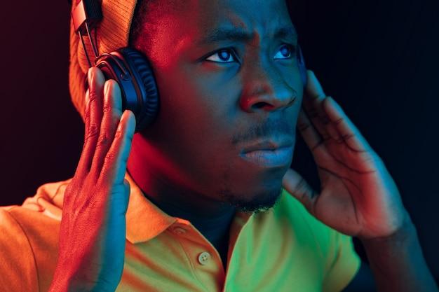 Der junge hübsche ernsthafte traurige hipster-mann, der musik mit kopfhörern im schwarzen studio mit neonlichtern hört. disco, nachtclub, hip-hop-stil, positive emotionen, gesichtsausdruck, tanzkonzept