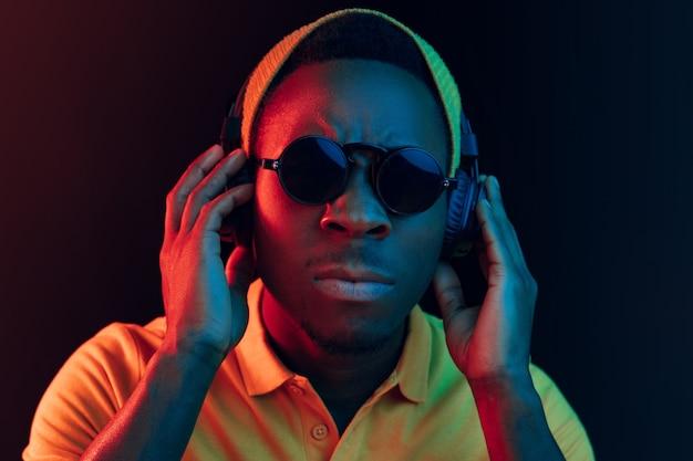 Der junge hübsche ernsthafte traurige hipster-mann, der musik mit kopfhörern im schwarzen studio mit neonlichtern hört.
