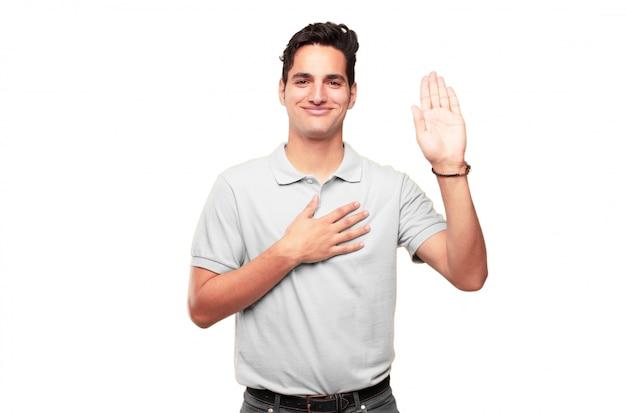 Der junge hübsche gebräunte mann, der sicher lächelt, wenn er ein aufrichtiges versprechen oder einen eid macht, schwören feierlich