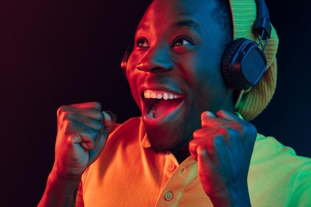 Der junge hübsche glückliche hipster-mann, der musik hört