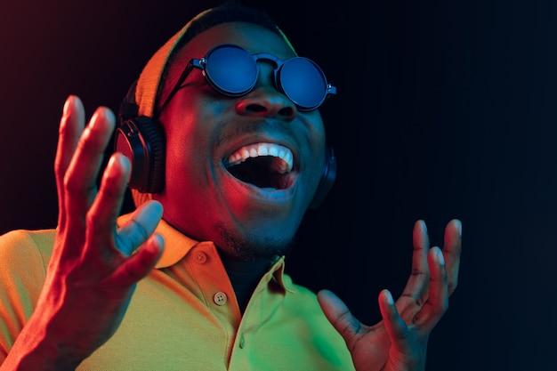 Der junge hübsche glückliche hipster-mann, der musik mit kopfhörern an schwarz mit neonlichtern hört