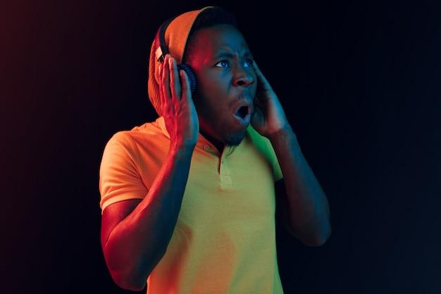 Der junge hübsche glückliche hipster-mann, der musik mit kopfhörern im schwarzen studio hört