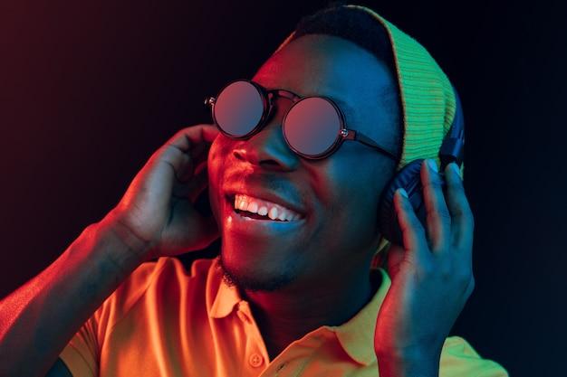 Der junge hübsche glückliche hipster-mann, der musik mit kopfhörern im schwarzen studio mit neonlichtern hört. disco, nachtclub, hip-hop-stil, positive emotionen, gesichtsausdruck, tanzkonzept