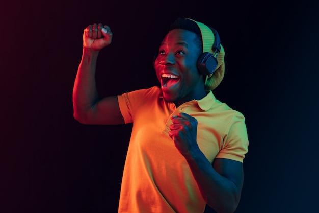 Der junge hübsche glückliche hipster-mann, der musik mit kopfhörern im schwarzen studio mit neonlichtern hört