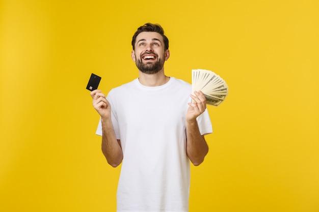 Der junge hübsche glückliche lächelnde mann, der scheckkarte hält und lösen seine hände ein, die auf gelb lokalisiert werden.