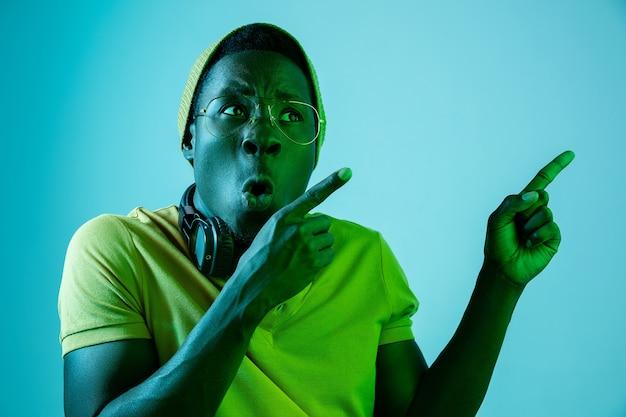 Der junge hübsche glückliche überraschte hipster-mann, der musik mit kopfhörern an mit neonlichtern hört
