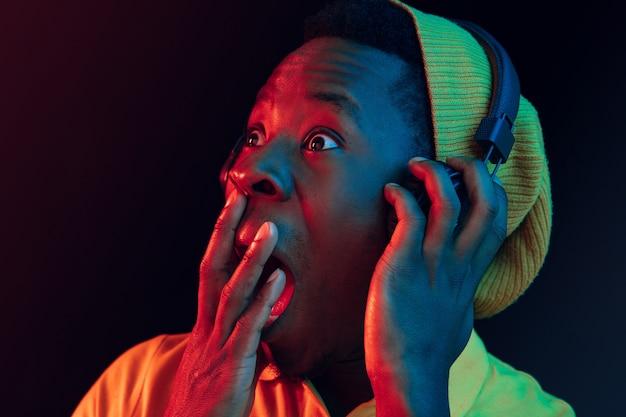 Der junge hübsche glückliche überraschte hipster-mann, der musik mit kopfhörern im schwarzen studio hört