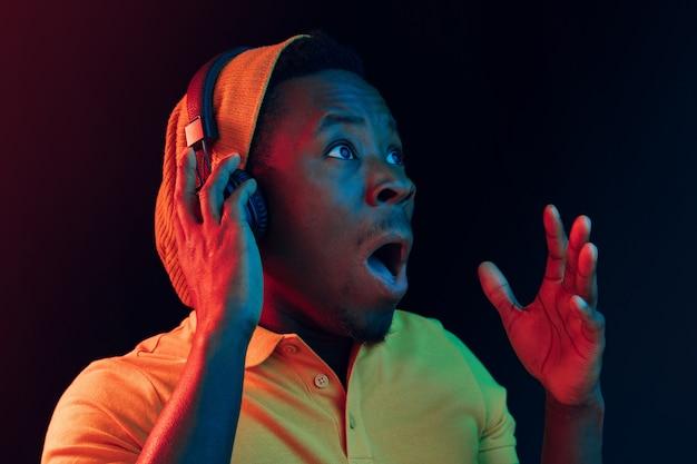 Der junge hübsche glückliche überraschte hipster-mann, der musik mit kopfhörern im schwarzen studio mit neonlichtern hört. disco, nachtclub, hip-hop-stil, positive emotionen, gesichtsausdruck, tanzkonzept