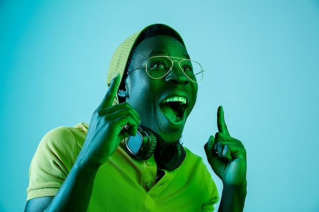 Der junge hübsche glückliche überraschte hipster-mann, der musik mit kopfhörern im studio mit neonlichtern hört. disco, nachtclub, hip-hop-stil, positive emotionen, gesichtsausdruck, tanzkonzept
