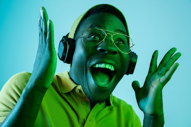 Der junge hübsche glückliche überraschte hipster-mann, der musik mit kopfhörern im studio mit neonlichtern hört.