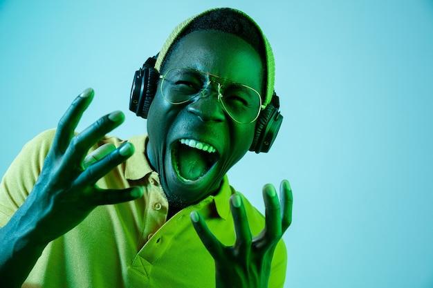 Der junge hübsche hipster-mann, der musik mit kopfhörern hört