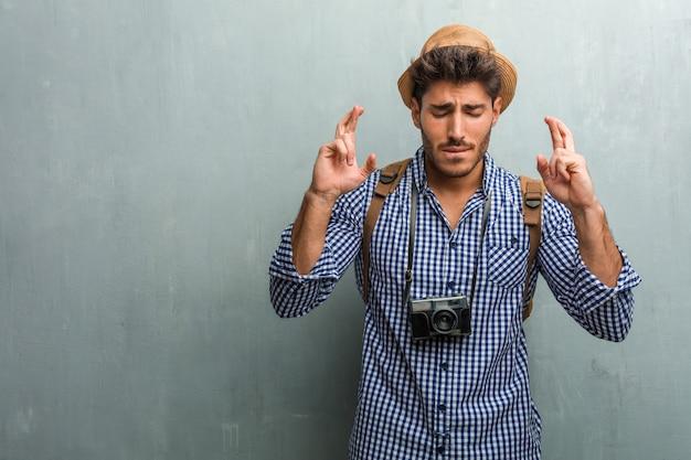 Der junge hübsche reisendermann, der einen strohhut, einen rucksack und eine fotokamera trägt, die seine finger kreuzt, möchte für zukünftige projekte glücklich sein, aufgeregt, aber besorgt, schließende augen des nervösen ausdrucks