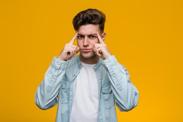 Der junge hübsche student, der ein denimhemd trägt, konzentrierte sich auf eine aufgabe und hielt ihn die zeigefinger, die kopf zeigen.