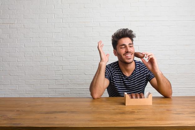 Der junge hübsche und natürliche mann, der auf einer tabelle sitzt und lacht und spaß hat, entspannt und nett ist, fühlt sich überzeugt und erfolgreich. schokoladen donuts essen.