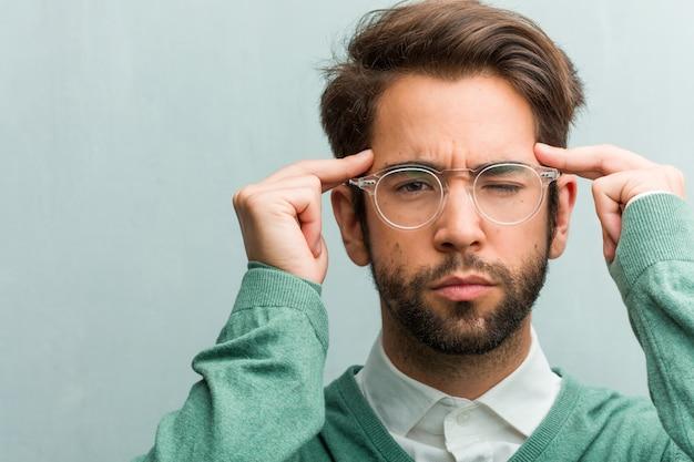 Der junge hübsche unternehmermanngesichts-nahaufnahmemann, der eine konzentrationsgeste macht, gerade schauend konzentriert auf ein ziel