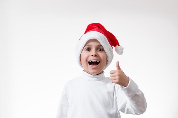 Der junge in der roten weihnachtsmütze lacht laut und zeigt seinen daumen. weihnachtskonzept.