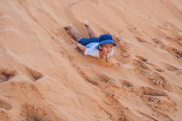 Der junge in der roten wüste im morgengrauen. reisen mit kindern konzept.