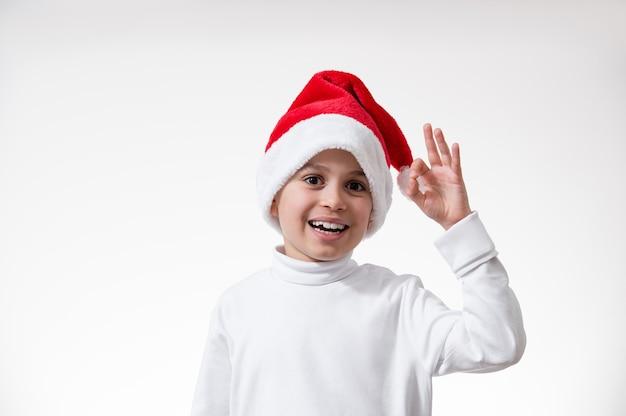 Der junge in einer roten weihnachtsmütze lächelt und zeigt eine geste von