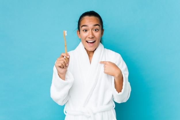 Der junge inder, der eine zahnbürste hält, überraschte das zeigen auf und lächelte breit