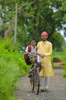 Der junge indische bauer und sein sohn gehen mit dem fahrrad zur schule