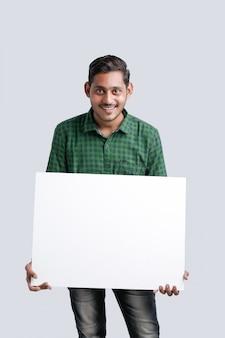 Der junge indische mann, der freien raum zeigt, singen brett über weißem hintergrund