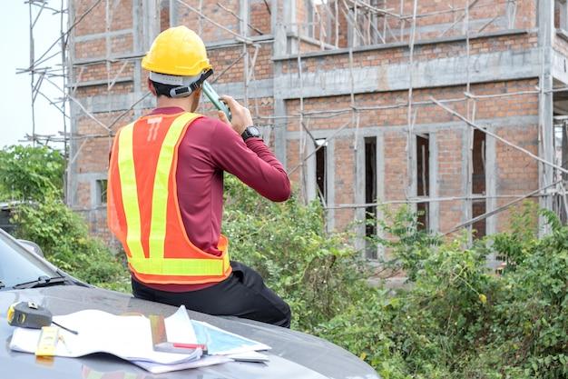 Der junge ingenieur spricht mit einem telefon vor einem unfertigen haus.