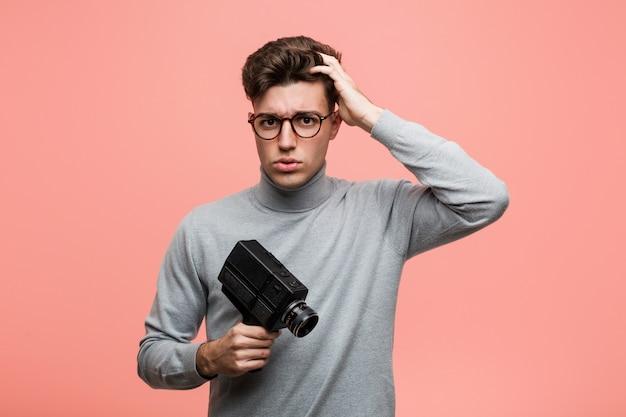Der junge intellektuelle mann, der eine filmkamera hält, die entsetzt ist, hat sich an wichtiges treffen erinnert.
