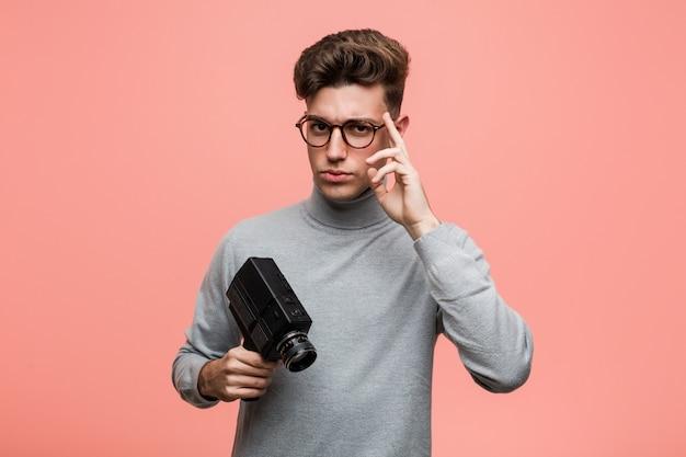 Der junge intellektuelle mann, der eine filmkamera zeigt seinen tempel mit dem finger hält und denkt, konzentrierte sich auf eine aufgabe.