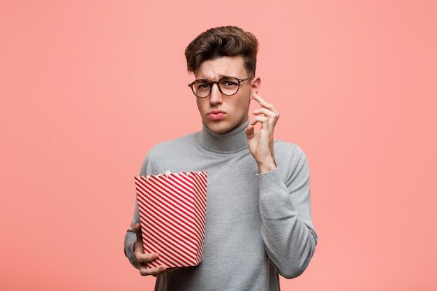 Der junge intellektuelle mann, der einen popcorneimer hält, der entsetzt wird, sie hat sich an wichtiges treffen erinnert.