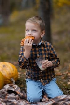 Der junge isst ein brötchen und trinkt milch im park