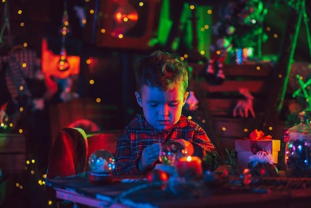 Der junge ist ein kind, die assistentin des weihnachtsmanns sitzt mit geschenken und spielzeug am tisch. rund um die fabelhafte weihnachtsdekoration.