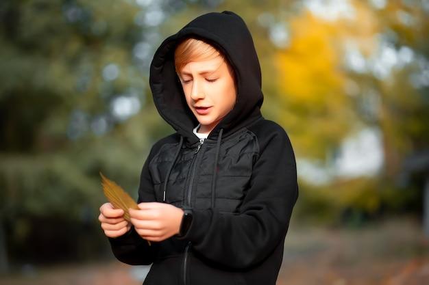 Der junge ist in einem schönen herbstpark, hält ein blatt in den händen und betrachtet es.