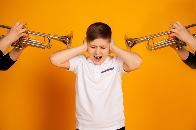 Der junge ist unzufrieden mit dem ärger eines lauten geräusches, er schloss die ohren mit den händen und schreit.