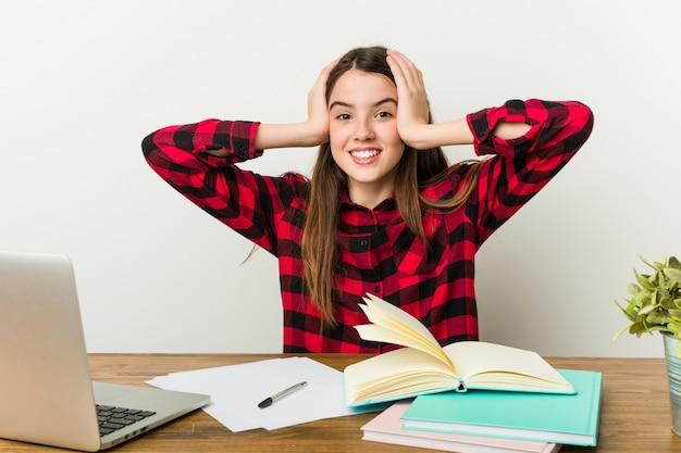 Der junge jugendliche, der zu ihrer routine erledigt hausaufgaben zurückgeht, lacht fröhlich.