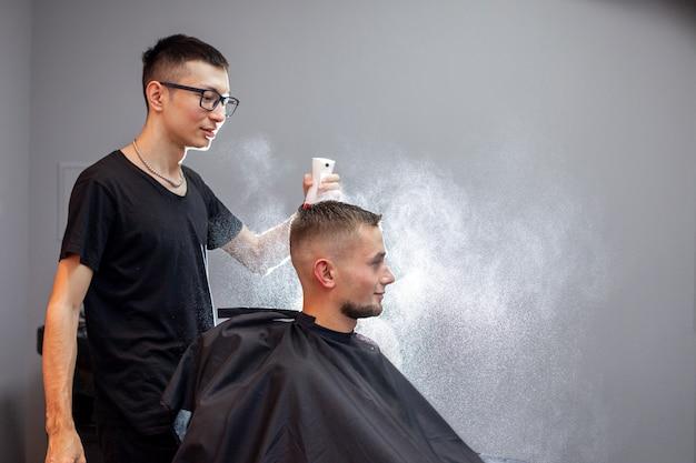Der junge kasachische friseur arbeitet in einem friseurladen