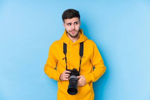 Der junge kaukasische fotografmann, der verwirrt lokalisiert wird, glaubt zweifelhaft und unsicher.