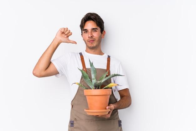 Der junge kaukasische gärtnermann, der eine anlage lokalisiert hält, fühlt sich stolz und selbstbewusst, beispiel zu folgen.