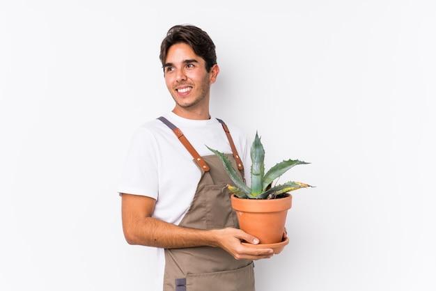 Der junge kaukasische gärtnermann, der eine anlage lokalisiert hält, schaut beiseite lächeln, nett und angenehm.