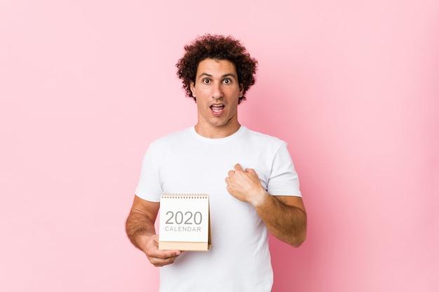 Der junge kaukasische gelockte mann, der einen kalender 2020 hält, überraschte das zeigen auf und breit lächelte.