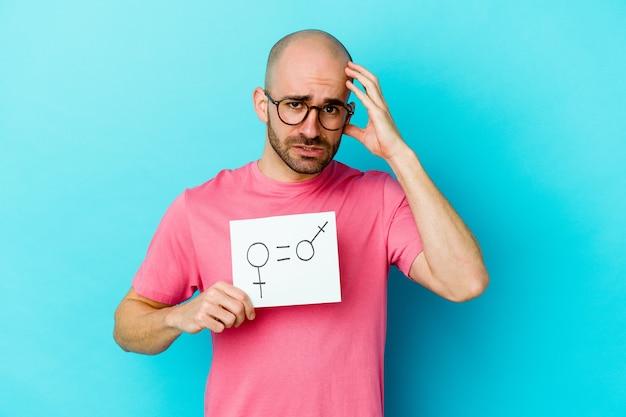 Der junge kaukasische glatzköpfige mann, der ein auf gelbem hintergrund isoliertes gleichstellungsschild hält, ist schockiert, sie hat sich an ein wichtiges treffen erinnert