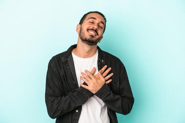 Der junge kaukasische mann, der auf blauem hintergrund isoliert ist, hat einen freundlichen ausdruck und drückt die handfläche auf die brust. liebe konzept.