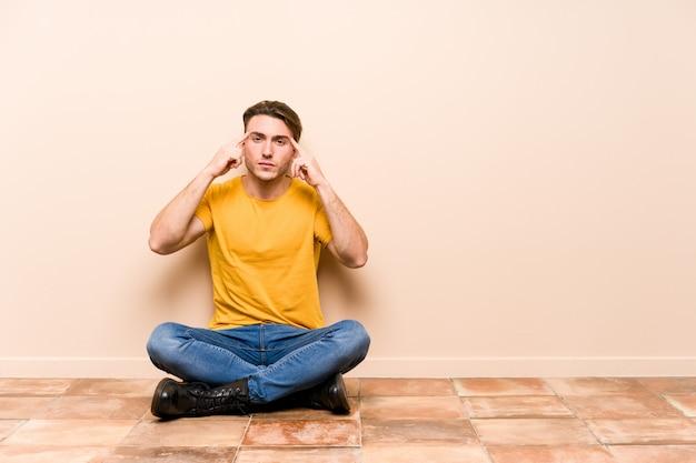 Der junge kaukasische mann, der auf dem boden lokalisiert sitzt, konzentrierte sich auf eine aufgabe und hielt die zeigefinger, die kopf zeigen.