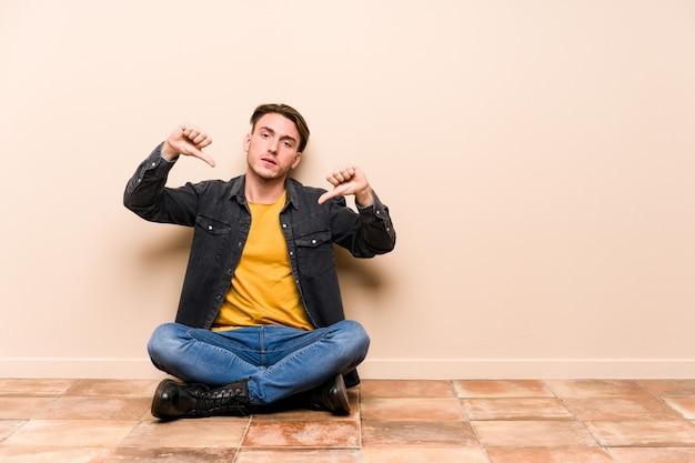 Der junge kaukasische mann, der auf dem boden sitzt, lokalisierte das zeigen des daumens unten und den ausdruck der abneigung.
