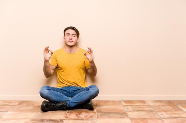 Der junge kaukasische mann, der auf dem lokalisierten boden sitzt, entspannt sich nach hartem arbeitstag, sie führt yoga durch.