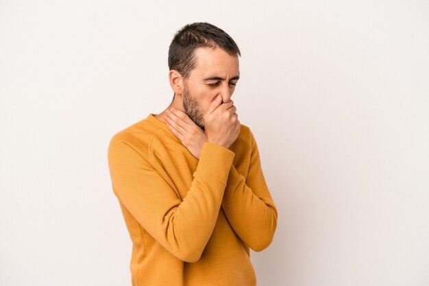 Der junge kaukasische mann, der auf weißem hintergrund isoliert ist, leidet aufgrund eines virus oder einer infektion unter schmerzen im hals.
