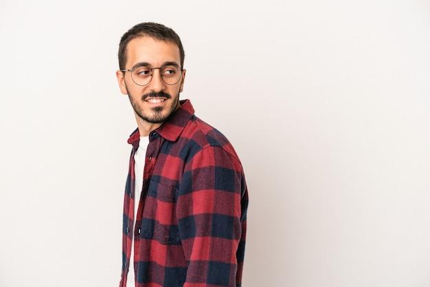 Der junge kaukasische mann, der auf weißem hintergrund isoliert ist, sieht beiseite lächelnd, fröhlich und angenehm aus.