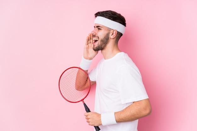 Der junge kaukasische mann, der badminton spielt, lokalisierte das schreien und das halten des nahen geöffneten munds der palme.