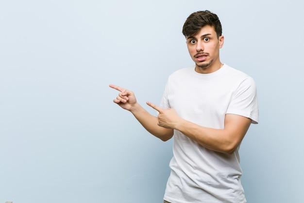 Der junge kaukasische mann, der ein weißes t-shirt trägt, entsetzte das zeigen mit den zeigefingern auf einen kopienraum.